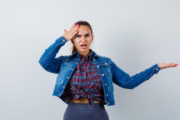 Jonge vrouw met de hand op het hoofd terwijl ze iets laat zien in een geruit hemd, jas, broek en verbaasd kijkt. vooraanzicht.