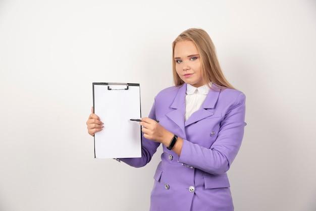 Jonge vrouw met de tablet van de potloodholding op wit.