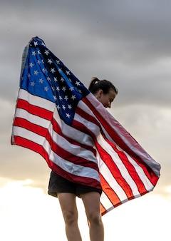 Jonge vrouw met de vlag van de verenigde staten genieten van zonsondergang in de natuur.