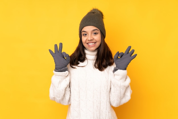 Jonge vrouw met de winterhoed op geïsoleerd geel die een ok teken met vingers toont