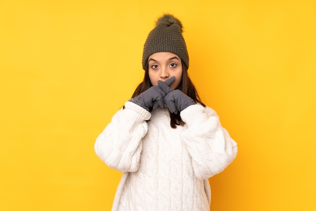 Jonge vrouw met de winterhoed op geïsoleerd geel die een teken van stilte-gebaar toont
