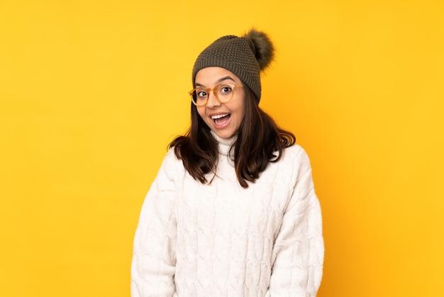 Jonge vrouw met de winterhoed op geïsoleerde geel met glazen en verrast