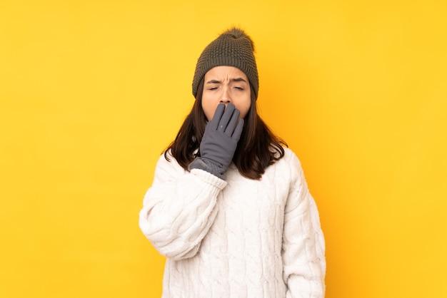 Jonge vrouw met de winterhoed op geïsoleerde gele geeuw
