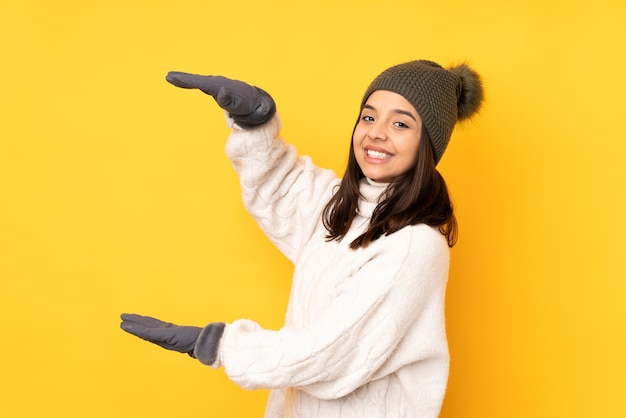 Jonge vrouw met de winterhoed op geïsoleerde gele holding copyspace om een advertentie in te voegen