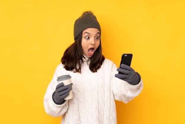 Jonge vrouw met de winterhoed op geïsoleerde gele holdingskoffie om mee te nemen en een mobiel