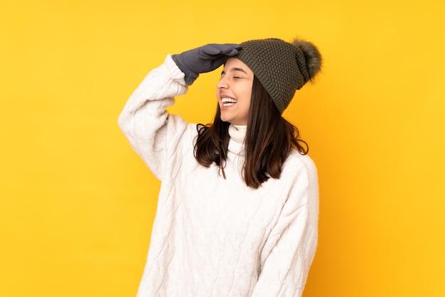 Jonge vrouw met de winterhoed op geïsoleerde gele veel glimlachen