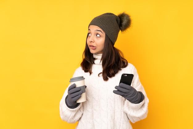Jonge vrouw met de winterhoed over geïsoleerde gele achtergrond die koffie houdt om mee te nemen en een mobiel terwijl hij iets denkt