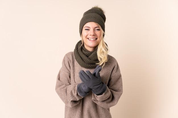 Jonge vrouw met de winterhoed over het geïsoleerde toejuichen