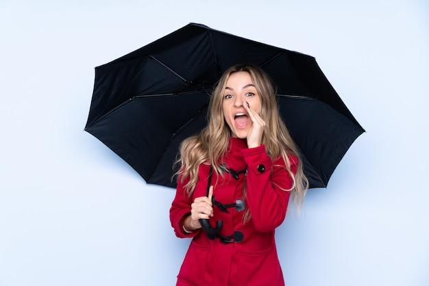 Jonge vrouw met de winterlaag en holding een paraplu schreeuwend met wijd open mond