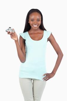 Jonge vrouw met digicam en hand op haar heup