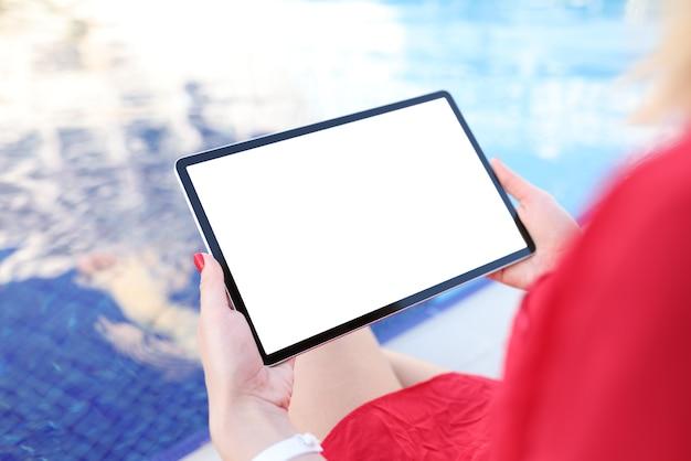 Jonge vrouw met digitale tablet met leeg scherm bij het zwembad