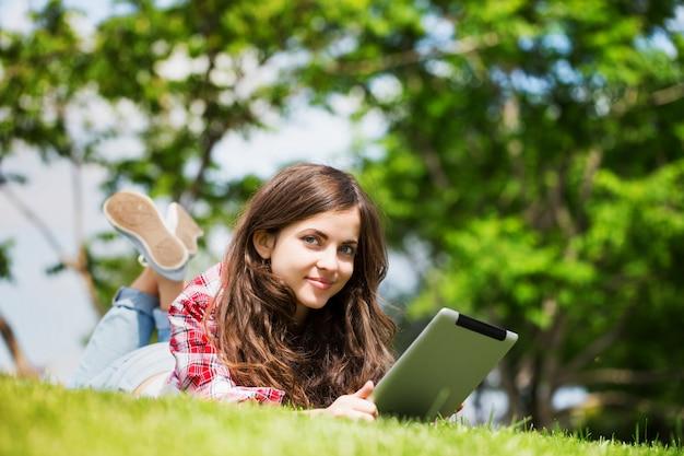 Jonge vrouw met digitale tablet op het gras