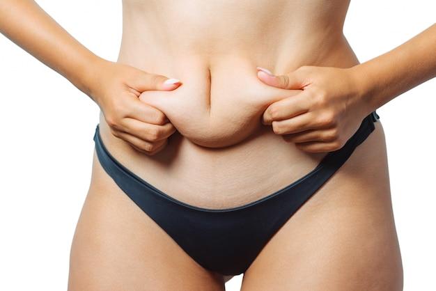 Jonge vrouw met dikke buik, te zwaar vrouwelijk lichaam dat op witte achtergrond, het schot van de close-upstudio wordt geïsoleerd. concept van een dieet, afvallen