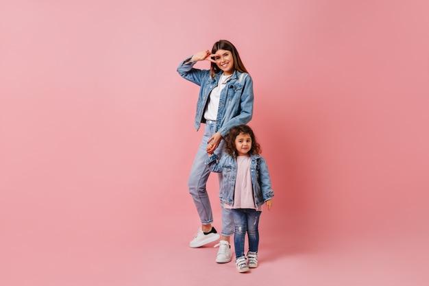 Jonge vrouw met dochter die vredesteken toont. studio shot van geweldige stijlvolle dame hand in hand met kind op roze achtergrond.