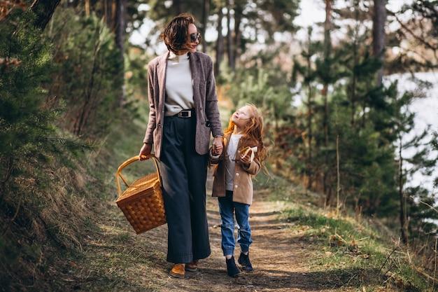 Jonge vrouw met dochter in bos met picknickdoos