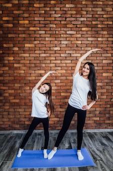 Jonge vrouw met dochter in sportkleding, legging en beha die yoga beoefent, mooi meisje staat... samen...