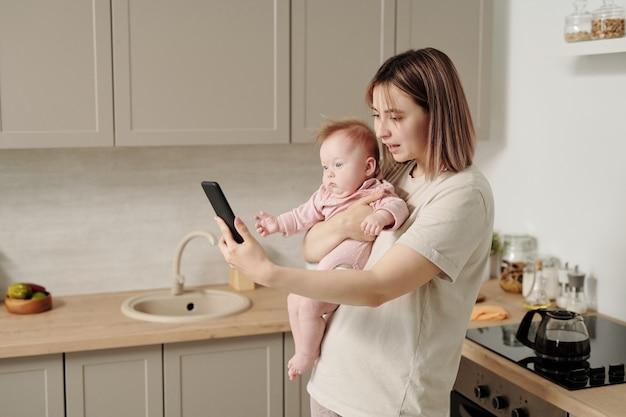 Jonge vrouw met dochtertje praten in videochat