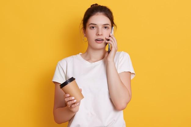 Jonge vrouw met donker haar die witte toevallige t-shirt dragen, die tegen gele muur stellen