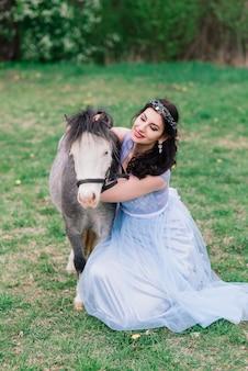 Jonge vrouw met donker haar in een mooie jurk loopt door het bos met een grijze pony