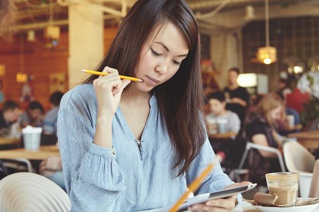 Jonge vrouw met donker haar met behulp van tablet in café