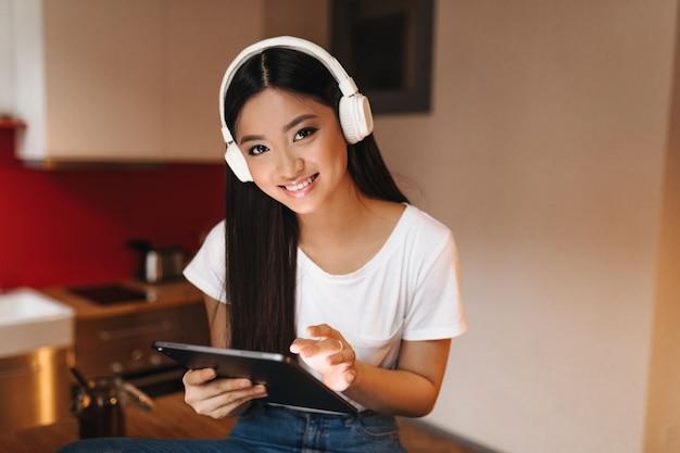 Jonge vrouw met donker haar met glimlach kijkt naar voren, houdt tablet vast en luistert naar muziek met een koptelefoon