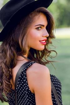 Jonge vrouw met donker krullend haar in stijlvolle elegante zwarte hoed poseren in het park