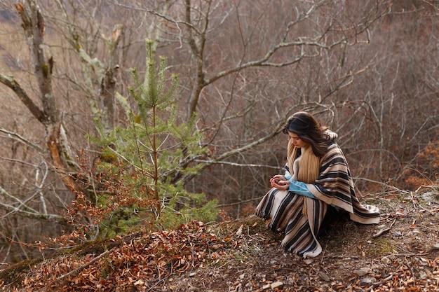 Jonge vrouw met donkerbruin haar in poncho wandelingen in de herfst bos