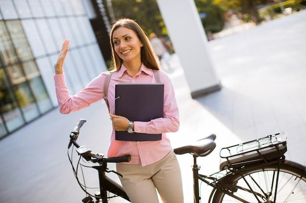 Jonge vrouw met dossiers in de handen die zich naast elektrische fiets bevinden