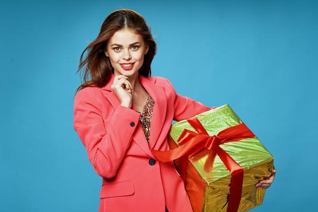 Jonge vrouw met dozen met geschenken in haar handen op een gekleurde achtergrond in mooie kleding, verkoop van geschenken, gelukkig kerstmis en nieuwjaar