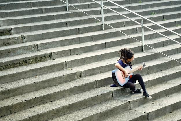 Jonge vrouw met dreadlocks alleen zittend op de trap buiten gitaar spelen.