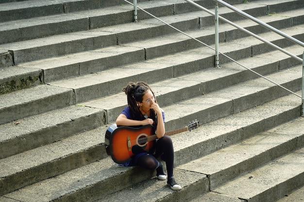 Jonge vrouw met dreadlocks alleen zittend op de trap in de lucht haar armen op de gitaar rustend.