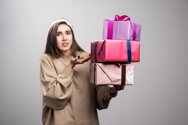 Jonge vrouw met drie dozen met kerstcadeautjes.