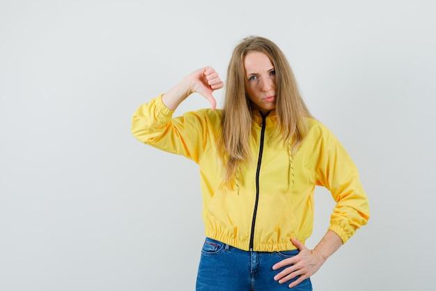 Jonge vrouw met duim naar beneden terwijl hand op taille in geel bomberjack en blauwe spijkerbroek en op zoek naar ontevreden, vooraanzicht.
