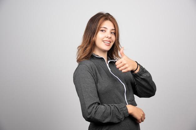 Jonge vrouw met duim omhoog tegen grijze muur.