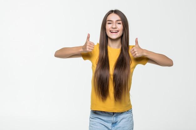 Jonge vrouw met duimen die omhoog over een witte muur wordt geïsoleerd
