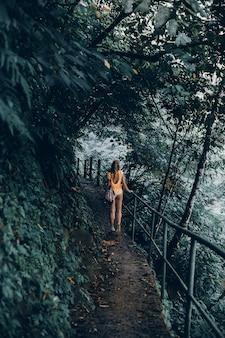 Jonge vrouw met een baard en een rugzak poseren in de jungle
