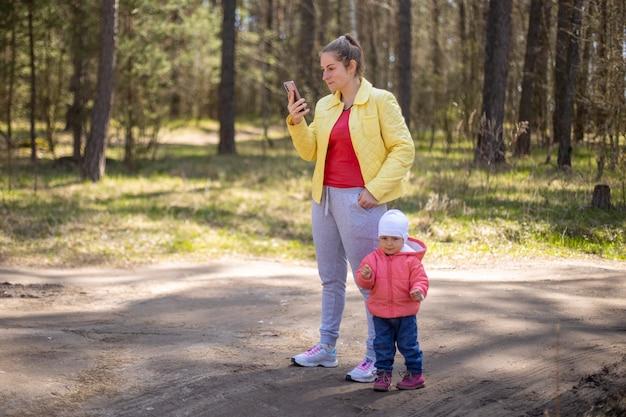 Jonge vrouw met een baby-peuter die emotioneel op een mobiele telefoon praat in een bos buiten de stad 4g