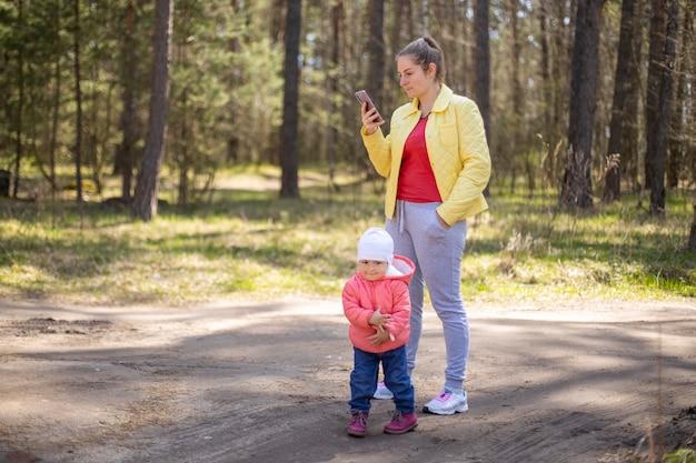 Jonge vrouw met een baby-peuter die emotioneel op een mobiele telefoon praat in een bos buiten de stad
