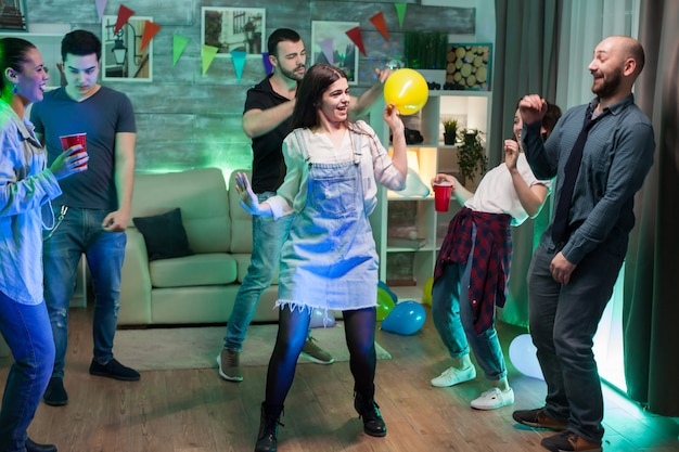 Jonge vrouw met een ballon met helium tijdens het dansen op het feest met haar vrienden.