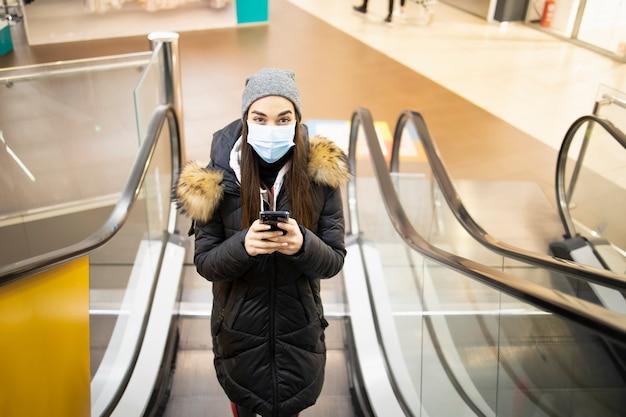 Jonge vrouw met een beschermend masker die de trap op een luchthaven neemt