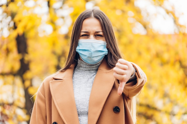Jonge vrouw met een beschermend masker in het de herfstpark