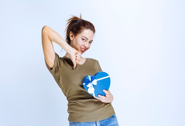 Jonge vrouw met een blauwe geschenkdoos in de vorm van een hart ziet er ontevreden uit