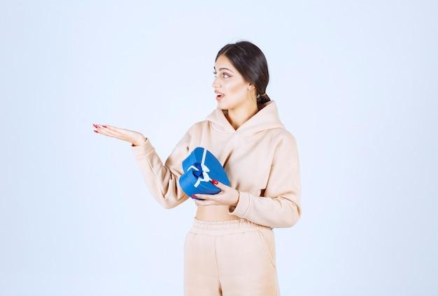 Jonge vrouw met een blauwe giftdoos die naar links wijst