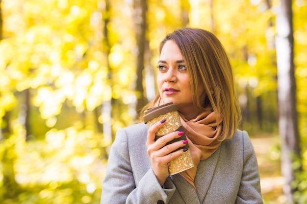 Jonge vrouw met een blauwe jas in het park