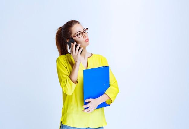 Jonge vrouw met een blauwe map die met de telefoon praat en er ontevreden uitziet