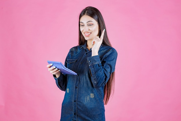 Jonge vrouw met een blauwe rekenmachine en denken