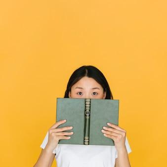 Jonge vrouw met een boek dat de camera bekijkt