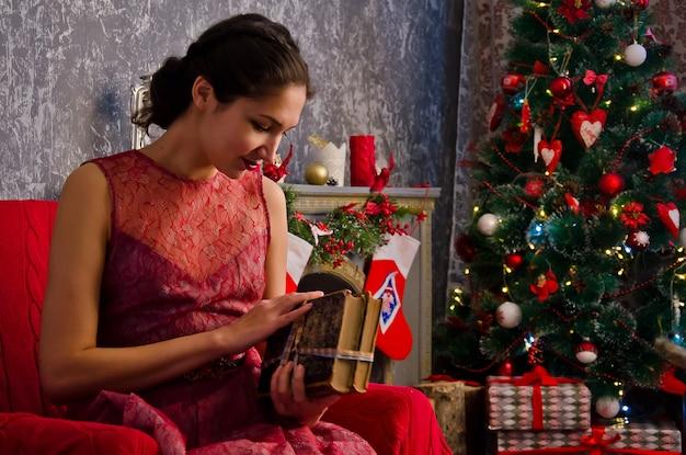 Jonge vrouw met een boek in handen dichtbij de kerstboom
