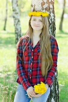 Jonge vrouw met een boeket van paardebloemen en een krans op haar hoofd