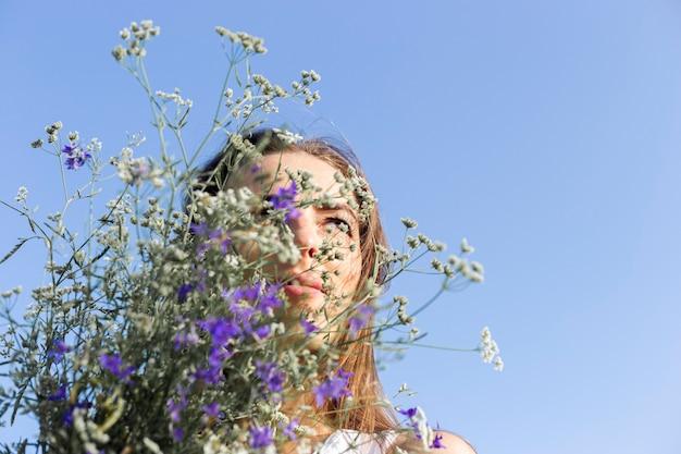 Jonge vrouw met een boeket van wilde bloemen op een blauwe hemelachtergrond.